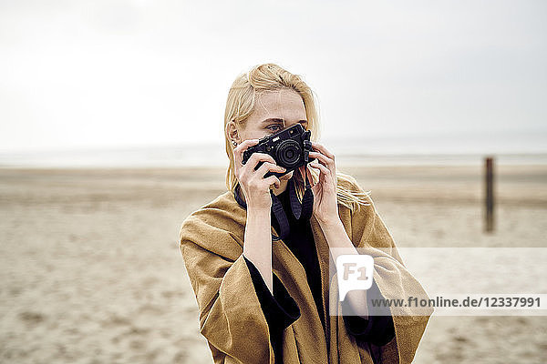 Netherlands  blond young woman taking photo with camera on the beach
