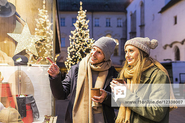 Young couple with cups of mulled wine looking at shop window at Christmas time