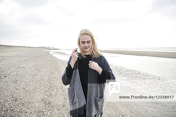 Netherlands  blond young woman wearing gray jacket on the beach