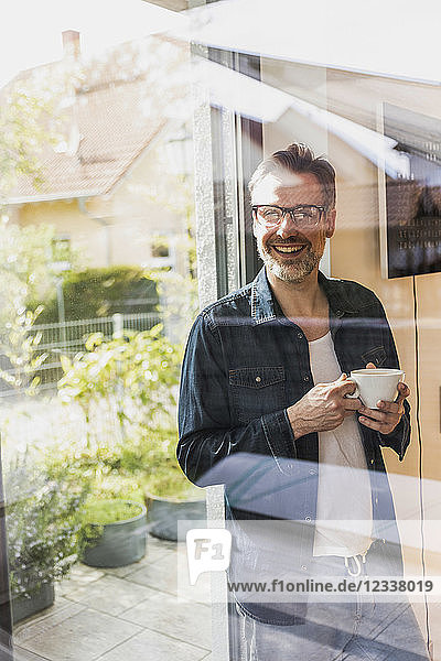 Portrait of laughing man with cup of coffee standing behind glass door at home
