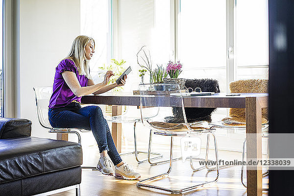 Woman sitting at table at home using tablet