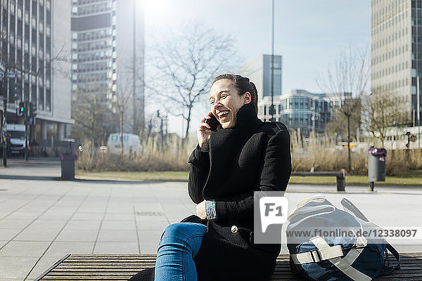 Germany  Essen  laughing young woman on the phone sitting on bench outdoors