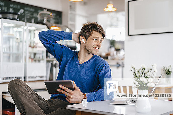 Smiling man in a cafe with earphone  laptop and tablet