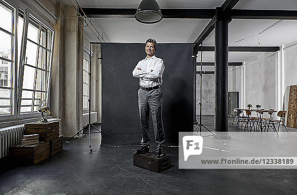 Portrait of mature businessman in front of black backdrop in loft