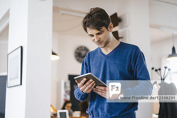 Man standing in a cafe looking at tablet