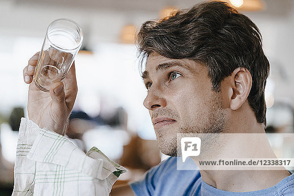 Man in a cafe examining glass