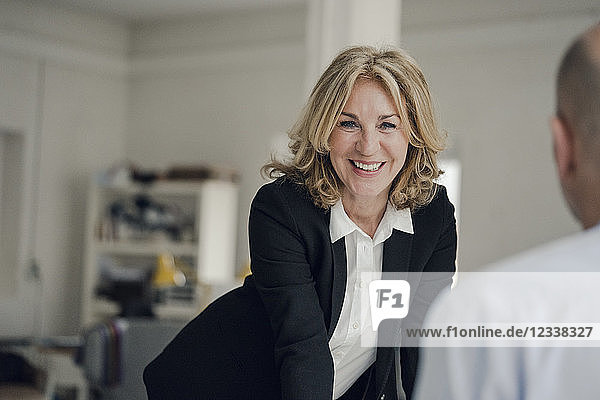 Smiling senior businesswoman looking at colleague