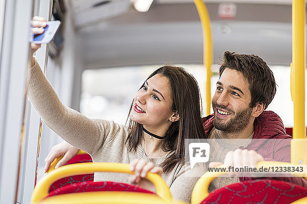 UK  London  portrait of smiling young couple taking selfie with smartphone in bus