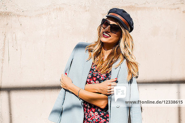 Stylish woman wearing sunglasses and cap in front of wall with arms folded