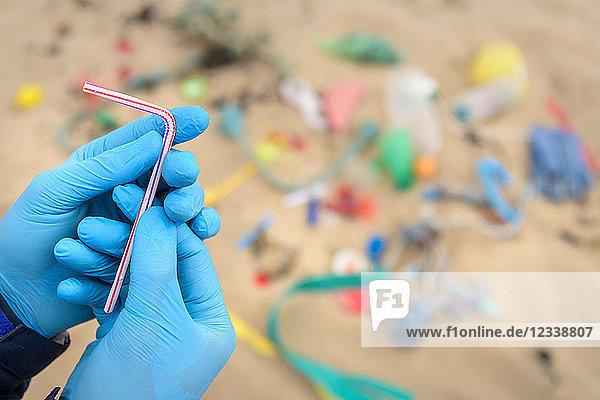 Mann hält Trinkhalm aus verschmutztem Plastik  der am Strand gesammelt wurde  Nordostengland  UK