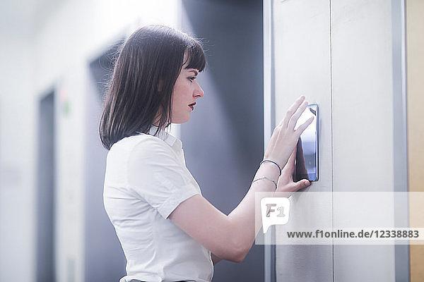 Frau mit wandmontiertem Touchscreen-Bedienfeld