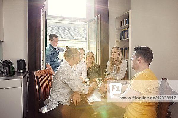 Eine Gruppe von Freunden unterhält sich bei einem Drink zu Hause