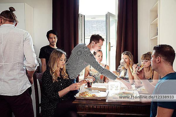 Eine Gruppe von Freunden unterhält sich bei Getränken und Pizza zu Hause