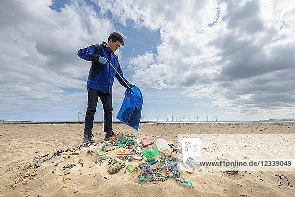 Mann sammelt am Strand gesammelte Kunststoffverschmutzung auf  Nordostengland  UK