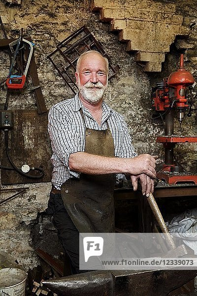 Blacksmith with hammer and anvil in blacksmiths shop  portrait