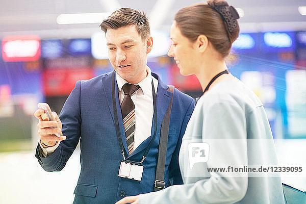 Geschäftsmann und Geschäftsfrau stehen zusammen und schauen auf das Smartphone