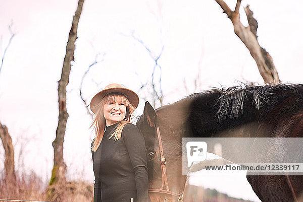 Porträt einer Frau mit Pferd  die lächelnd in die Kamera schaut
