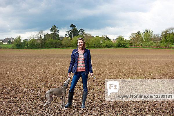 Mittlere erwachsene Frau und Whippet-Hund im Feld  Porträt