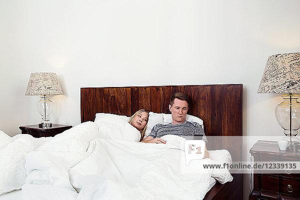Im Bett liegendes Paar mit Mobiltelefon