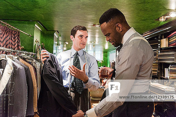 Tailor and customer looking at suit jacket in traditional tailors shop