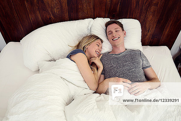 Couple lying in bed snuggling