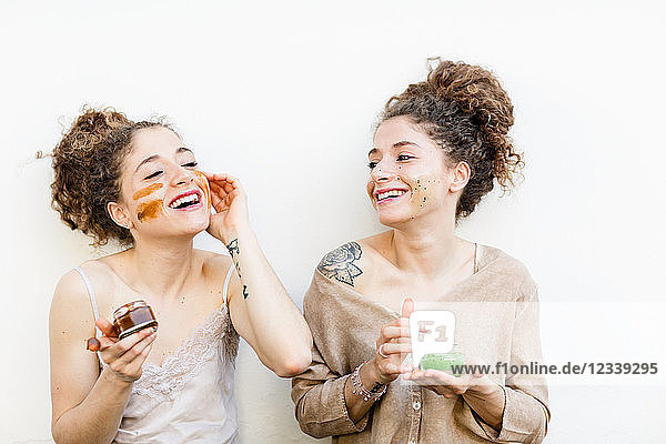 Fashion blogger twins applying face masks  white background