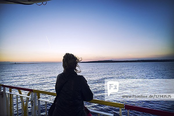 Silhouette of unrecognizable woman on the deck of a ferry boat in port. Mediterranean Coast  Mahon  Menorca  Balearic Islands  Spain