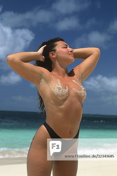 Bare-chested young woman with a sandy imprint of hand on breasts  Grenadines islands  Saint Vincent and the Grenadines  Winward Islands  Lesser Antilles  Caribbean Sea.