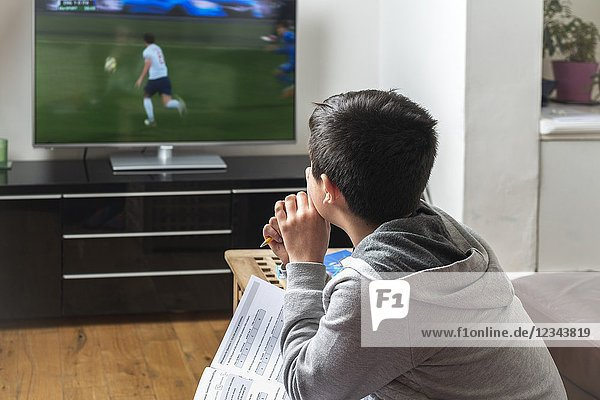 UK-Schoolboy  10 years old  trying to study while watching football match on TV.