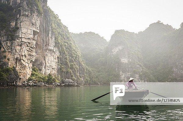 Vietnamese boatman in the karst landscape of Ha Long Bay  Quang Ninh Province  Vietnam. Ha Long Bay is a UNESCO World Heritage Site.