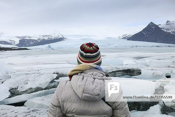 Woman staring Fjallsarlon glacier in Vatnajokull park Iceland.