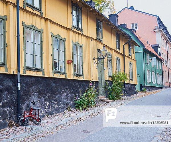 Mobility walking frame locked to lampost in Langa Gatan (Long Street)  Djurgarden  Stcokholm  Sweden  Scandinavia.Langa Gatan is a street of old traditional wooden houses.