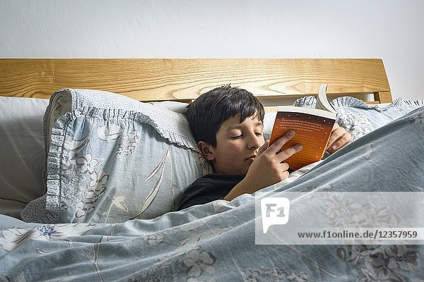 Boy reading book in bed   Harry Potter by J. K. Rowling   UK.