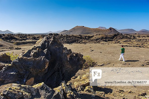 Tourist woman. Volcanic landscape  Timanfaya National Park. Lanzarote Island. Canary Islands Spain. Europe.