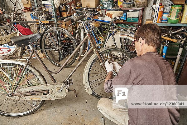 A technician restoring a vintage bicycle.