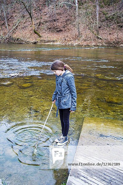 Caucasian beautiful girl wearing a black leggings and white and black jacket. She is in playing in the water in a river during the fall with a wood stick and making circles. Vertical photo.