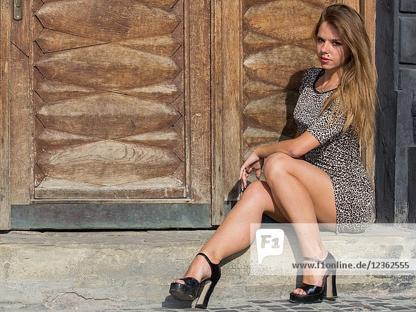Sexy and elegant Ukrainian woman wearing a leopard skin print dress posing seated and reclining to one side in front of a large wooden door for a photographic sequence in the ancient city of Lviv  Ukraine.