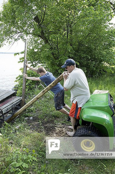 Father and teen son using the leverage of long poles to push lakeside dock into place. Clitherall Minnesota MN USA.