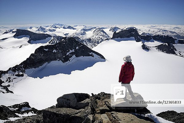 Norway  Oppland  Vaga  Jotunheimen National Park  trekker at the summit of Galdhopiggen  the tallest mountain in Norway and Scandinavia at 2469m  Model Released.