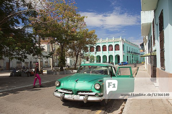 Old American car in front of the colonial house at the historic center with the Policlinico Docente Jose Marti Perez Health Center at the background  Camagüey  Cuba  West Indies  Central America.