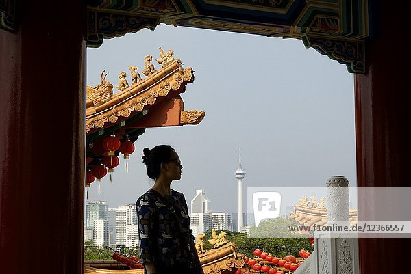 Malaysia  Selangor State  Kuala Lumpur  woman at Thean Hou Chinese Temple  KL tower (Menara Kuala Lumpur) in the background  Model Released