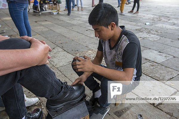 A boy is shining shoes on the square in front of the Cathedral of Our Lady of the Assumption in the city of Oaxaca de Juarez  Oaxaca  Mexico.