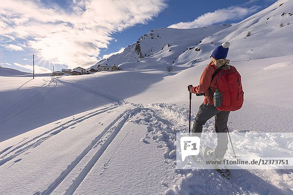 Young girl walks with snowshoes in the fresh snow at sunset.Grevasalvas  Engadin Valley  Graubünden  Switzerland  Europe.