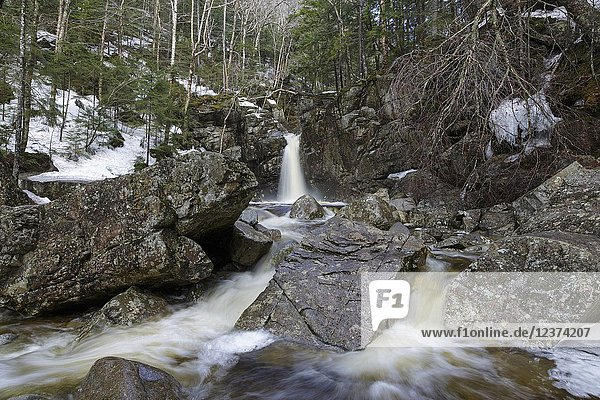 Kinsman Falls on Cascade Brook in Lincoln  New Hampshire during the spring months. These falls are located along the Basin-Cascades Trail  and are also known as Basin Falls and Tunnel Falls.