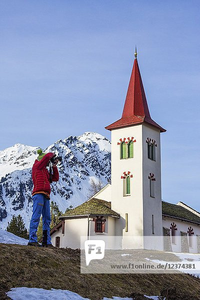 Photographer in action while the church tower frames the snowy peaks Maloja Pass Canton of Graubunden Switzerland.