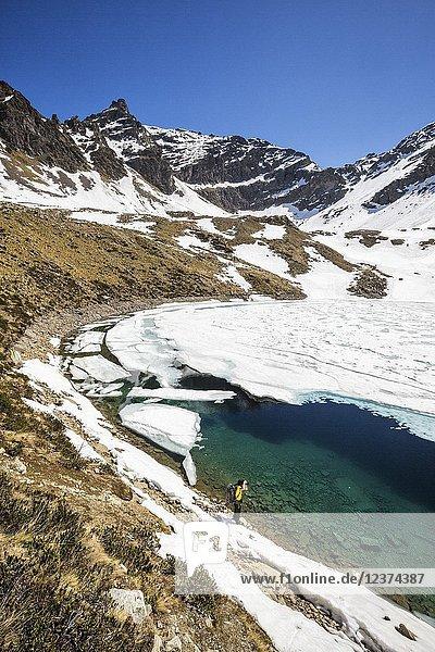 Photographer at Laj dal Teo where snow begins to melt due to spring thaw Poschiavo Valley Canton of Graubunden Switzerland.