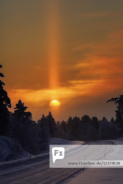 Sun pillar optical effect photographed near Muonio,  Lapland,  Finalnd,  Europe.