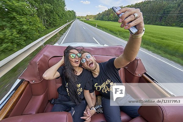 Adventurous couple taking selfie while driving in luxury oldtimer. Turkish ethnicity. High society. Bloggers Adem Bayalan and Emine Feruz Bayalan. Bavaria  Germany.