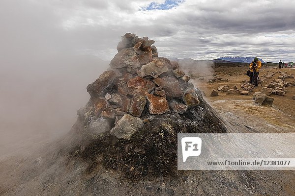 Photographer with mud pots  steam vents  and sulphur deposits at HveraroÌ. nd  north coast of Iceland.