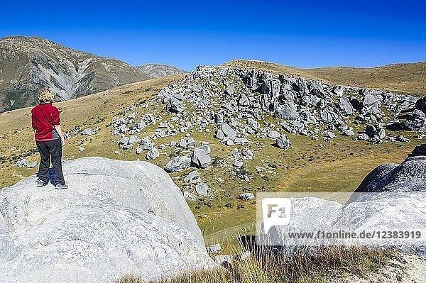 Wanderin steht auf den Kalksteinfelsen von Castle Hill  Südinsel  Neuseeland  Ozeanien
